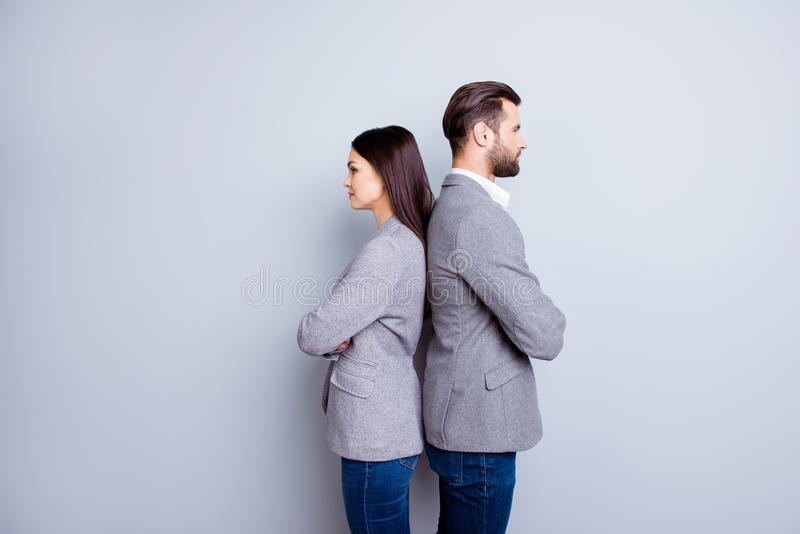 Two professionals in business and finance in gray jackets and jeans standing back-to-back on gray backdrop royalty free stock photo