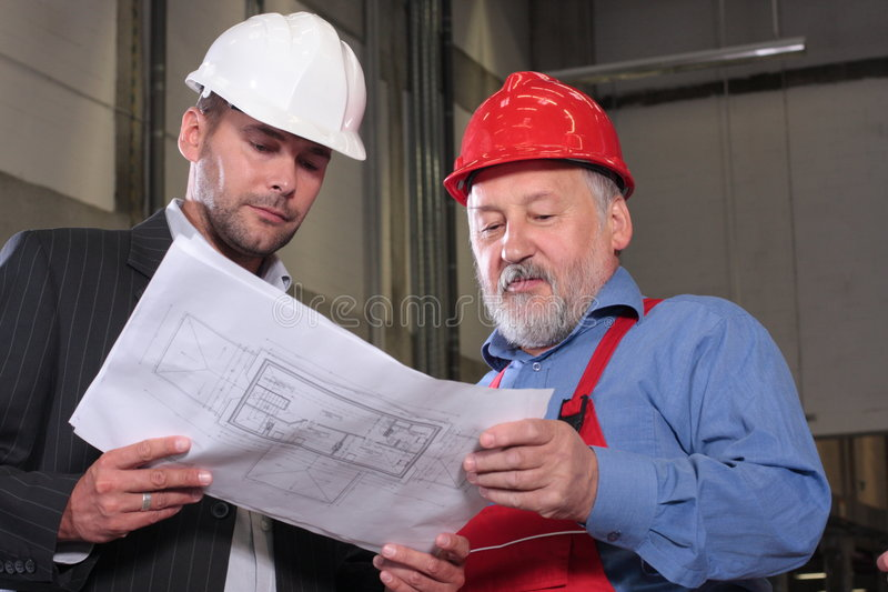 Two Professionals With Set Of Blueprints Royalty Free Stock Images