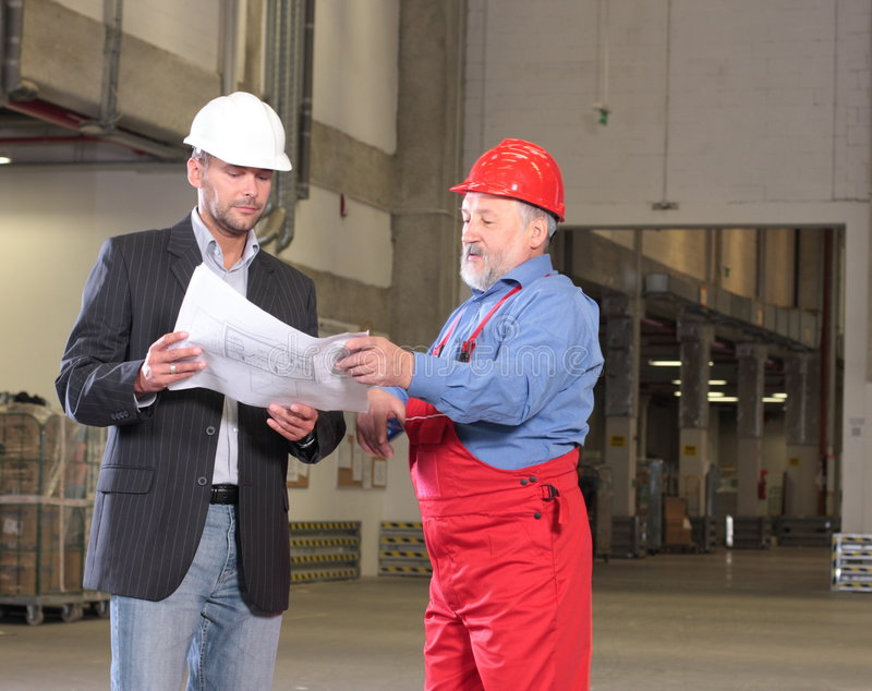 Two professionals with set of blueprints royalty free stock photos
