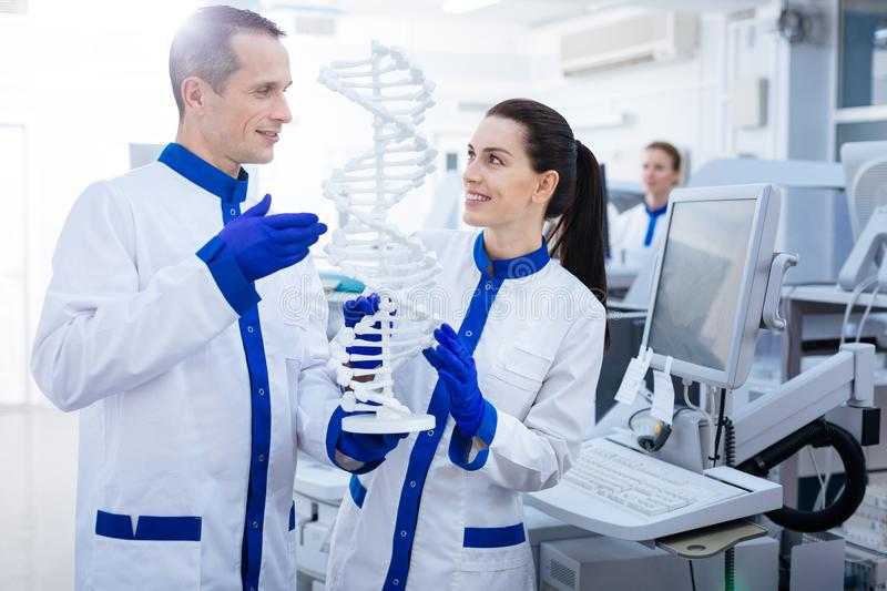 Two promising lab assistants looking for DNA mutation. Abnormal DNA. Pleased genuine Mal and female laboratory assistants want to find out mutation while looking stock photo