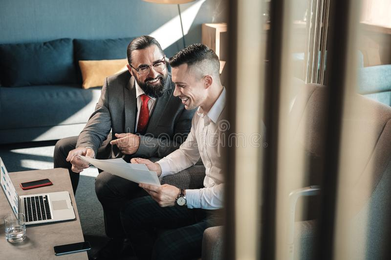 Two prosperous business partners laughing while communicating. Laughing and communicating. Two prosperous business partners laughing while communicating with stock images