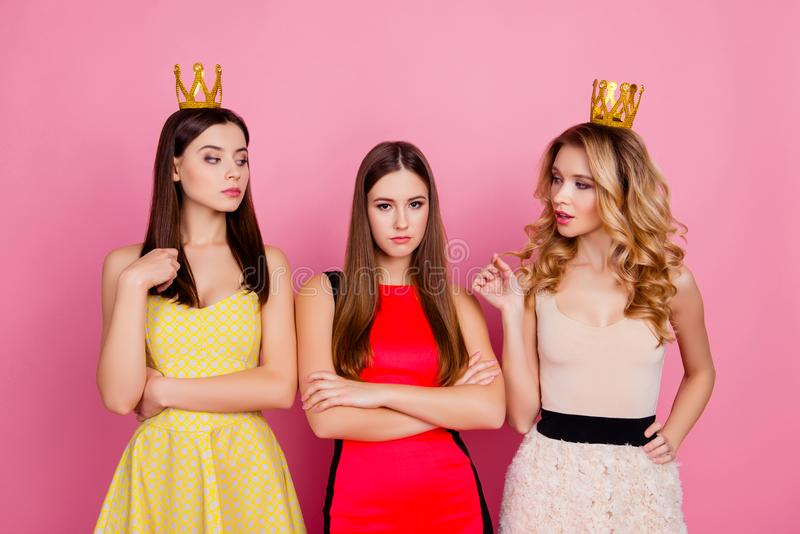 Two proud girls in gold crowns on head looking arrogantly to the royalty free stock photos