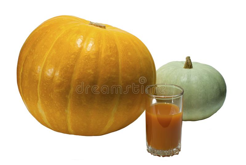 Two pumpkins and a glass of pumpkin juice isolated royalty free stock photography