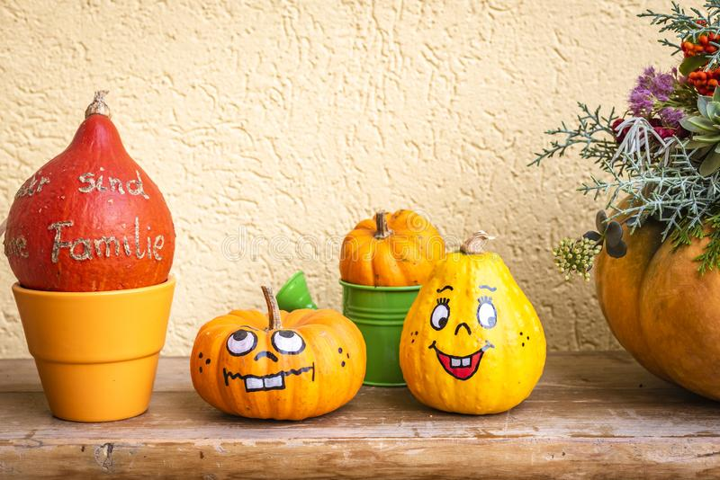 Two pumpkins with face. Before a yellow wall stock image