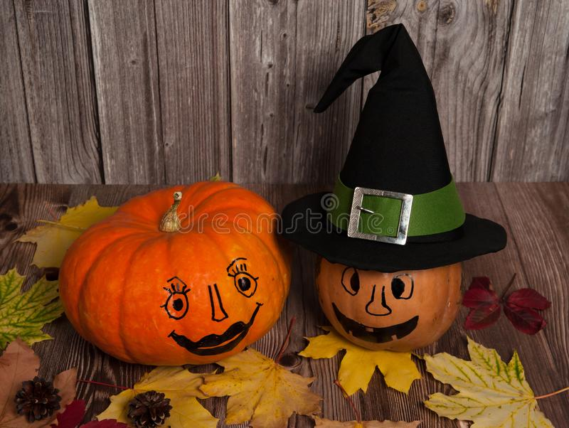 Two pumpkins with funny painted faces, a magic witch hat, cones and colorful autumn leaves on a wooden background. royalty free stock images