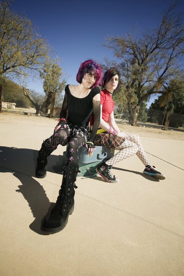 Two Punk Girls Sitting on Suitcases. Two Punk Girls Sitting on Stacked Suitcases stock photography