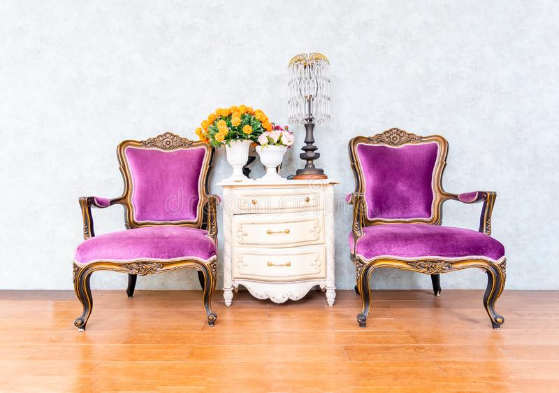 Two purple armchairs sofa couch classical style. And vintage white wooden , retro furniture and decoration in living room stock photography
