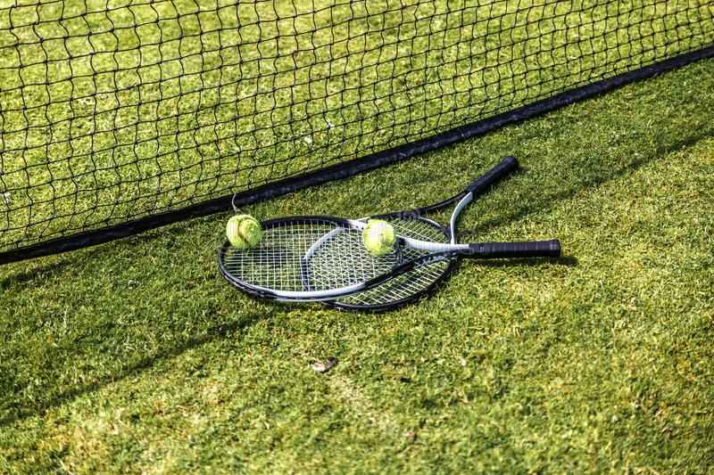 Two rackets and two tennis balls next to the net of a green tennis court stock photos