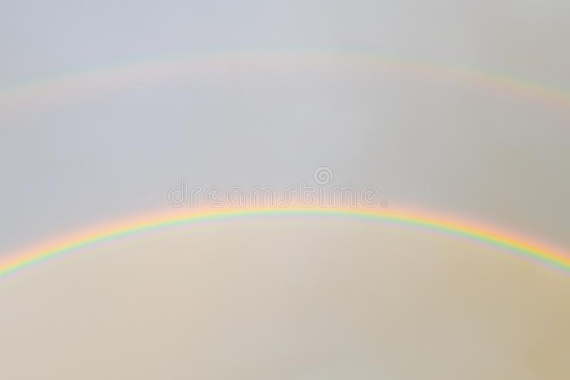 Two rainbows in the sky. Bright rainbows dancing in the light air clouds above and the foggy sky after rain below. natural shot royalty free stock photo