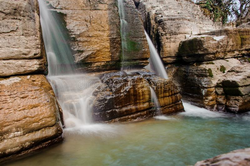 Two rapid waterfall streams flowing down the rock in Martvili canyon on autumn day. Two rapid waterfall streams flowing down the rock into a river in Martvili stock photos