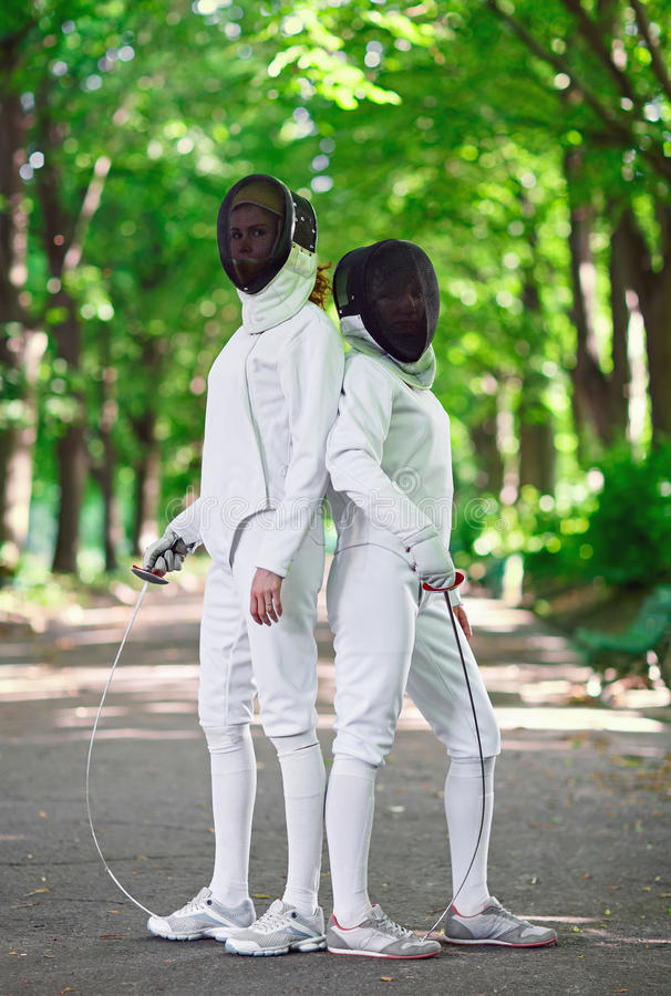 Two rapier fencers women staying in park alley. Getting ready for competition stock photos