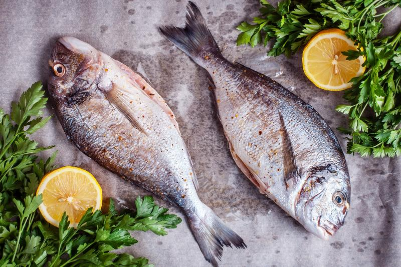 Two raw dorado fish with spices and lemon. Top view stock images