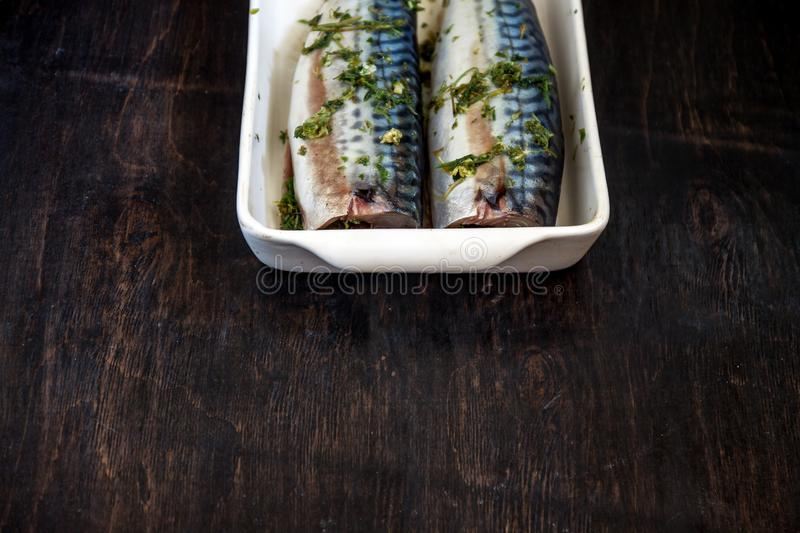 two raw fish mackerel in greens and herbs will be baked on a dark background. View from above. Retro effect stock images