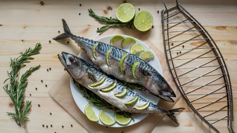 Two raw fresh mackerel fishes with lime on white dish on wooden royalty free stock photos