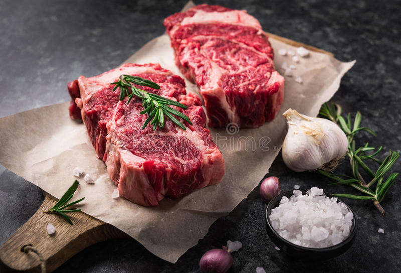 Two raw fresh marbled meat black angus steak ribeye, garlic, salt stock images