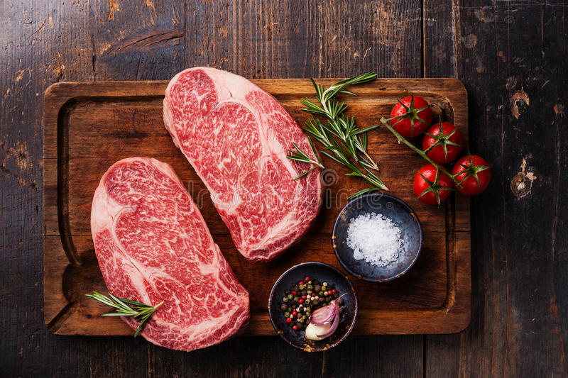 Two Raw fresh marbled meat Black Angus Steak Ribeye. And seasonings on dark wooden background stock photo