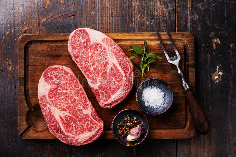 Two Raw fresh marbled meat Steak Ribeye. Two Raw fresh marbled meat Black Angus Steak Ribeye, seasonings and meat fork on dark wooden background royalty free stock photos