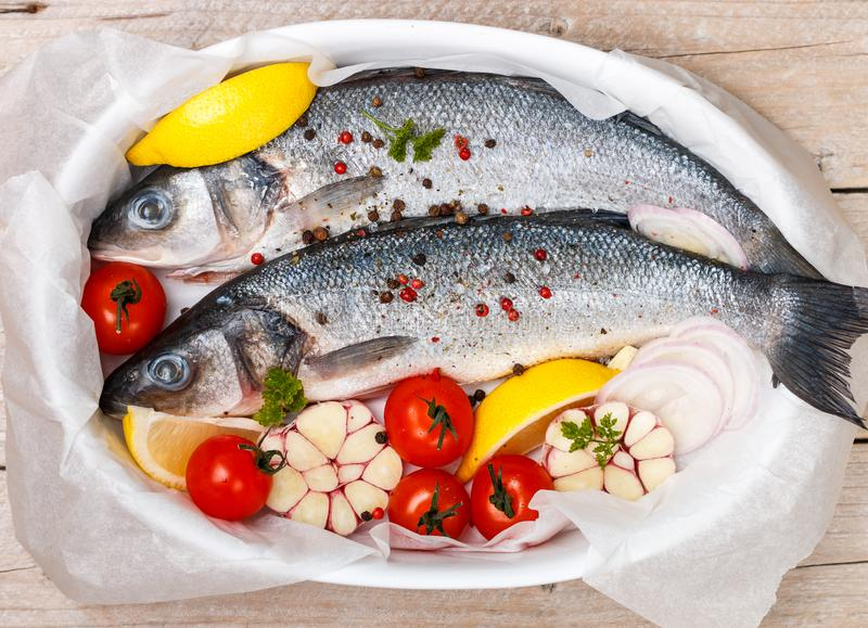 Two raw fresh sea bass ready for baking with tomatoes, lemon, red onion, garlic, ginger, parsley and spices stock images