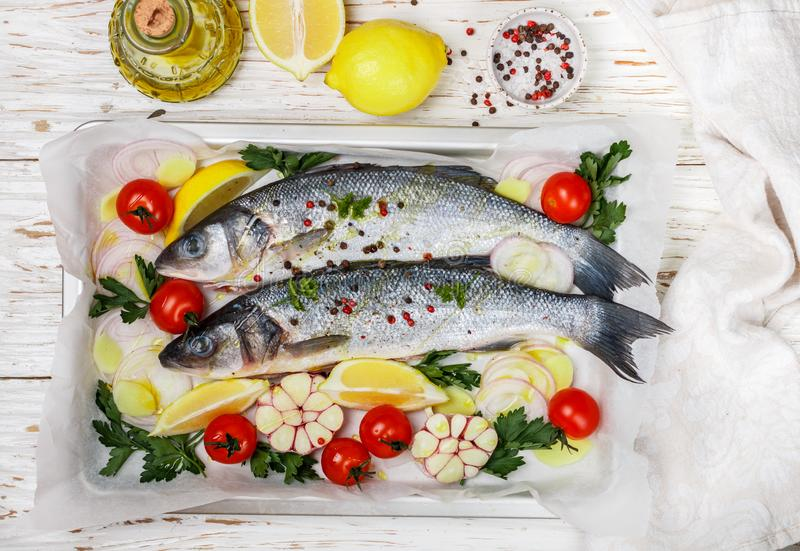 Two raw fresh sea bass ready for baking with tomatoes, lemon, red onion, garlic, ginger, parsley and spices. Prepare a tasty and healthy lunch or dinner in a royalty free stock photography