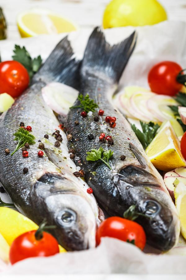 Two raw fresh sea bass ready for baking with tomatoes, lemon, red onion, garlic, ginger, parsley and spices. Prepare a tasty and healthy lunch or dinner in a stock image