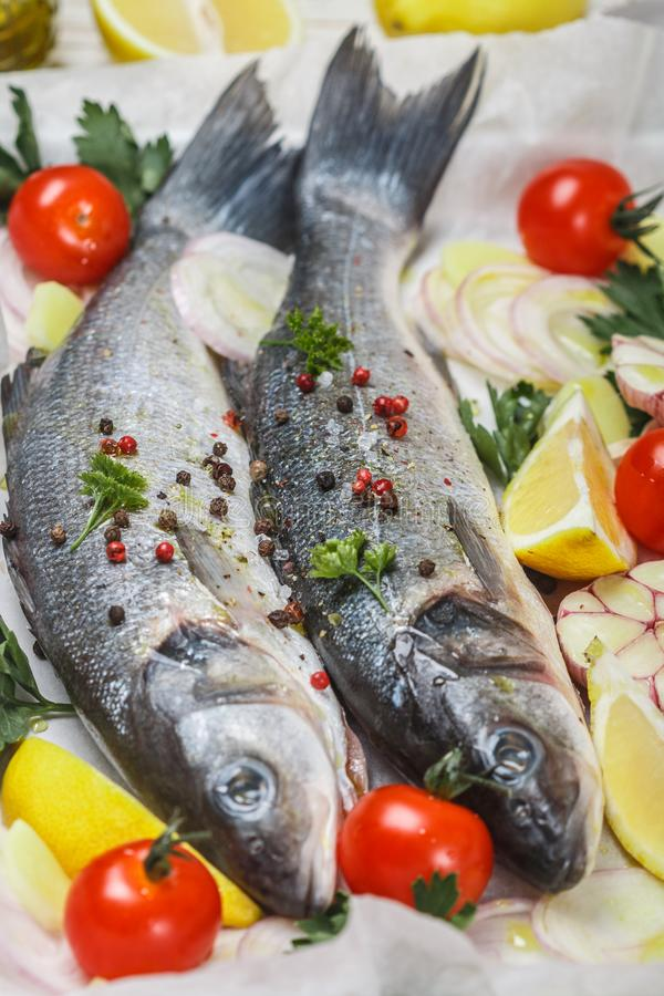 Two raw fresh sea bass ready for baking with tomatoes, lemon, red onion, garlic, ginger, parsley and spices. Prepare a tasty and. Healthy lunch or dinner in a stock photo