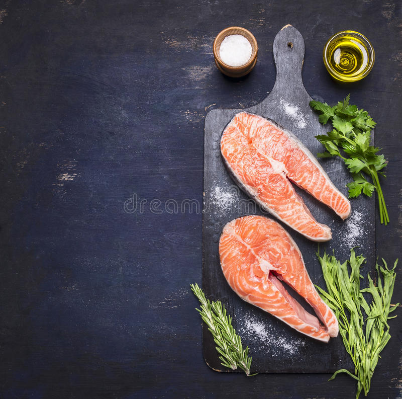 Two raw steak to salmon, seafood, healthy food with herbs, parsley, olive oil and salt dark vintage cutting board on wooden rus. Two raw steak to salmon, seafood royalty free stock photo