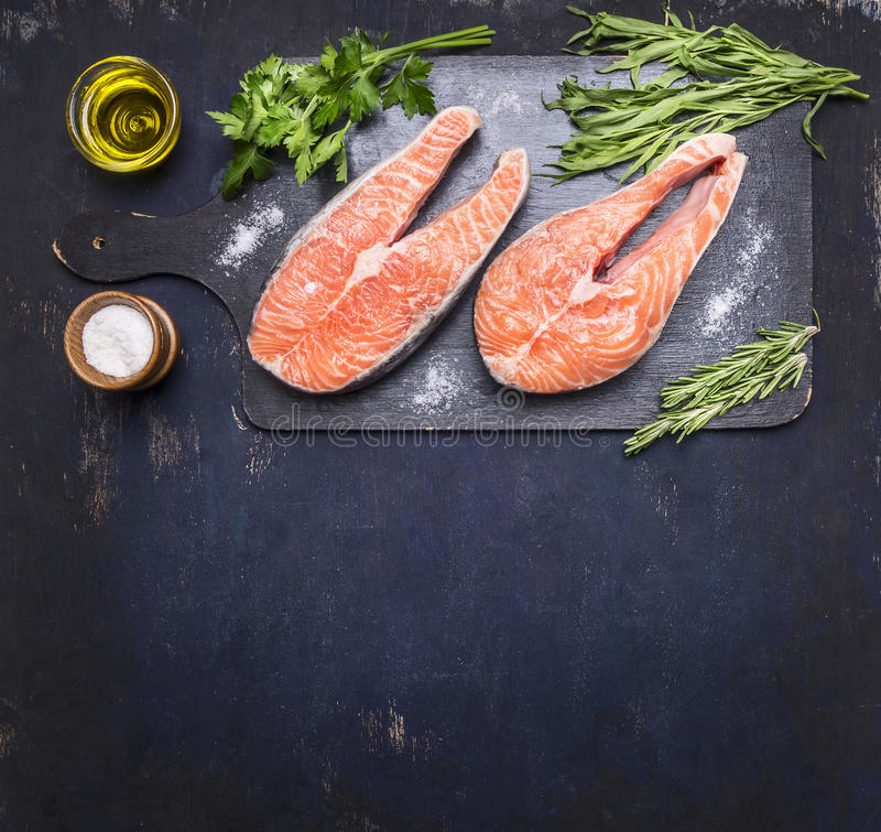 Two raw steak to salmon, seafood, healthy food with herbs, parsley, olive oil and salt dark vintage cutting board on wooden rus. Two raw steak to salmon, seafood stock photos