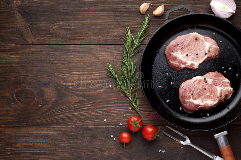Two raw steaks on frying pan on rustic wooden background. Pieces of meat ready for cooking. Top view, copy space royalty free stock image