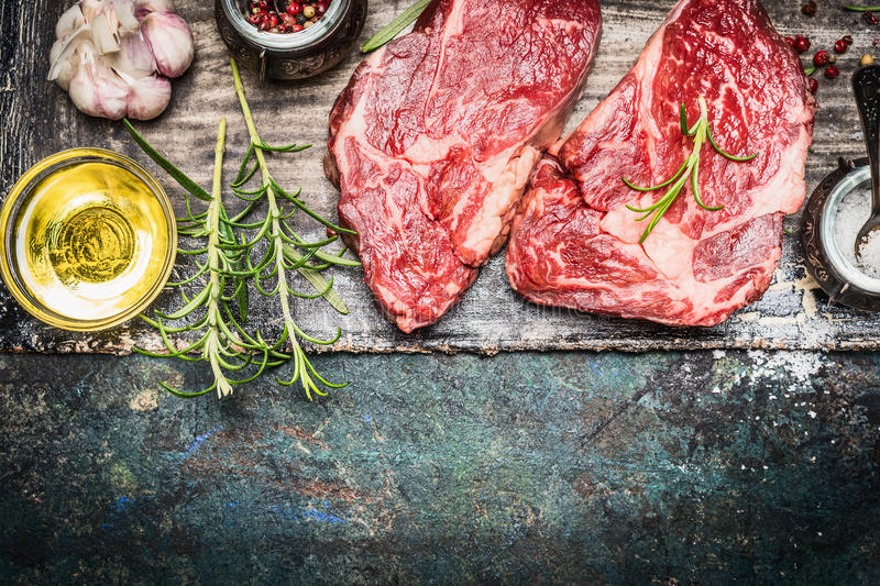 Two raw steaks with oil and spices on dark rustic background, top view. Border stock images