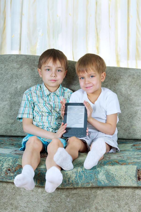 Two reading boys. With electronic book royalty free stock photos
