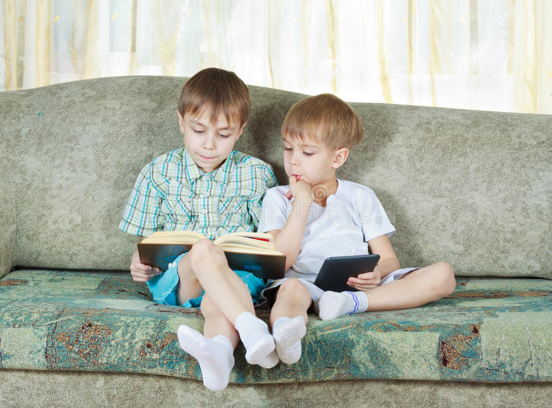 Two reading boys. With paper and electronic book royalty free stock photos