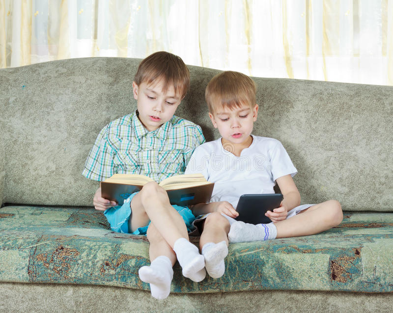Two Reading Boys. With Paper And Electronic Book Royalty Free Stock Images