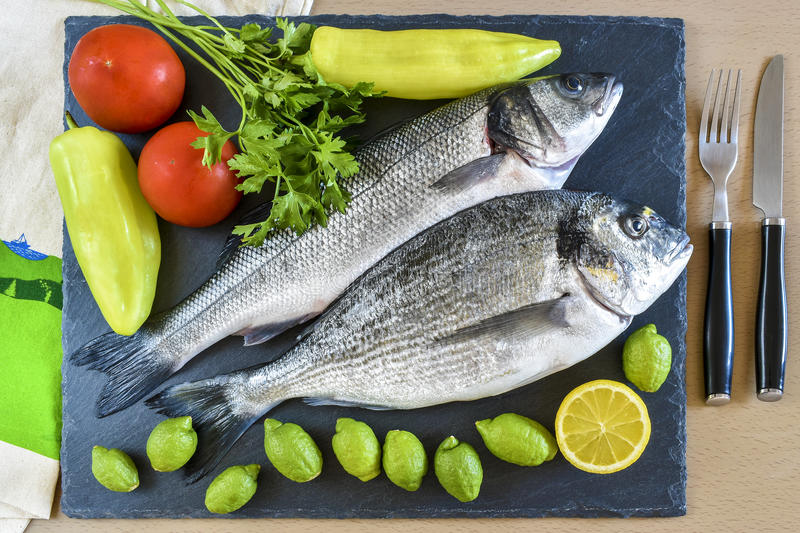 Two ready to cook raw fish with lemon and tomatoes on stone slat. E board. Top view stock photo