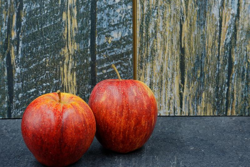 Two red apples on an old stone worktop stock photography