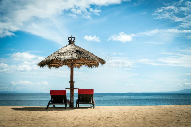 Two red beach chairs under wicker umbrella on a coast. Idyllic holiday landscape concept stock image