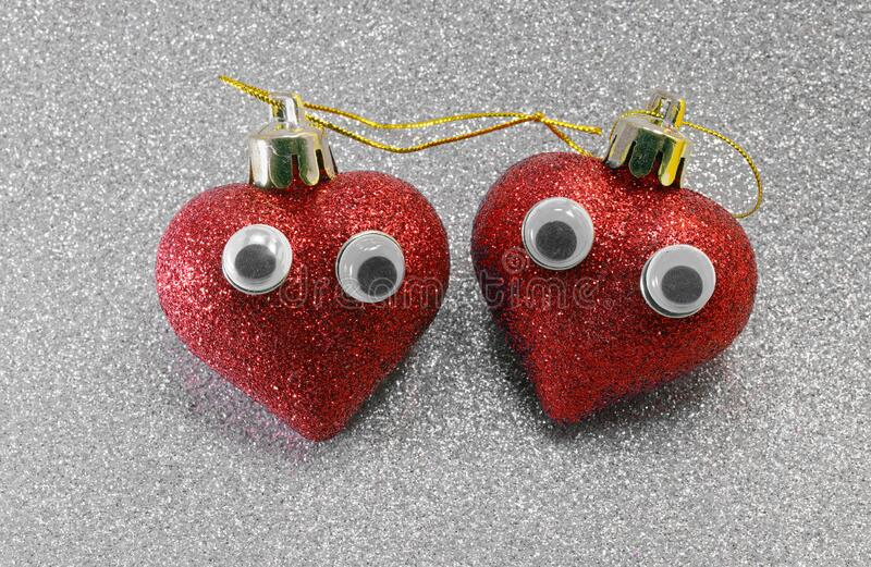 Two hearts with eyes on silver background. Two red big hearts with eyes on the bright silver color background ideal as a conceptual idea of love stock photography