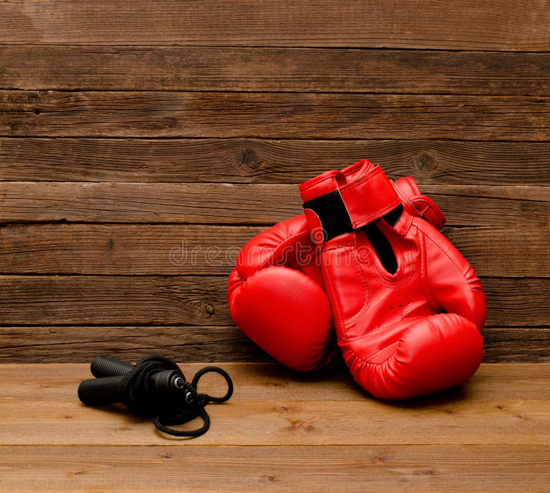Two red boxing gloves lie on a wooden brown background, skipping rope. Empty space royalty free stock photos