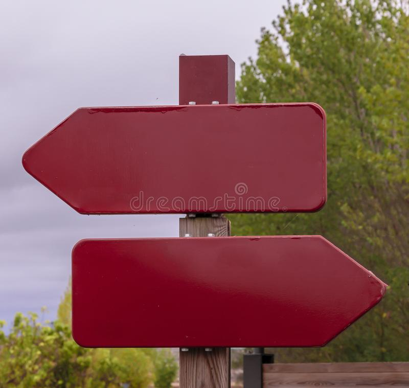 Two red burgundy signs without text pointing opposite directions royalty free stock photos