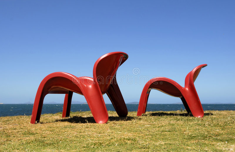 Two red chairs. At the sea side stock photography