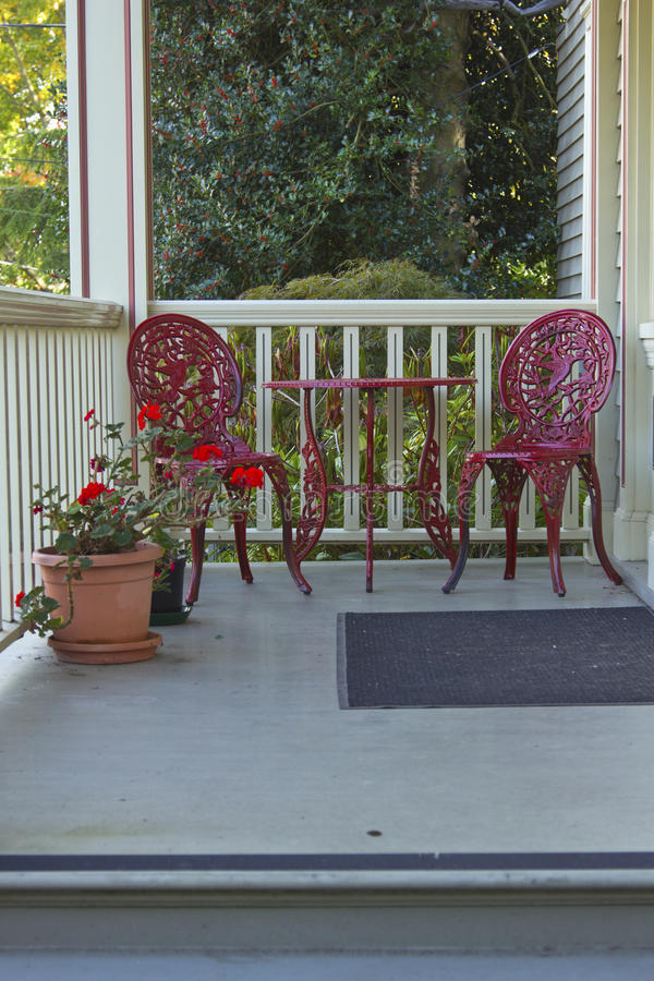 Two red chairs and a table. Two red chairs a flower pot and a table on a porch stock image