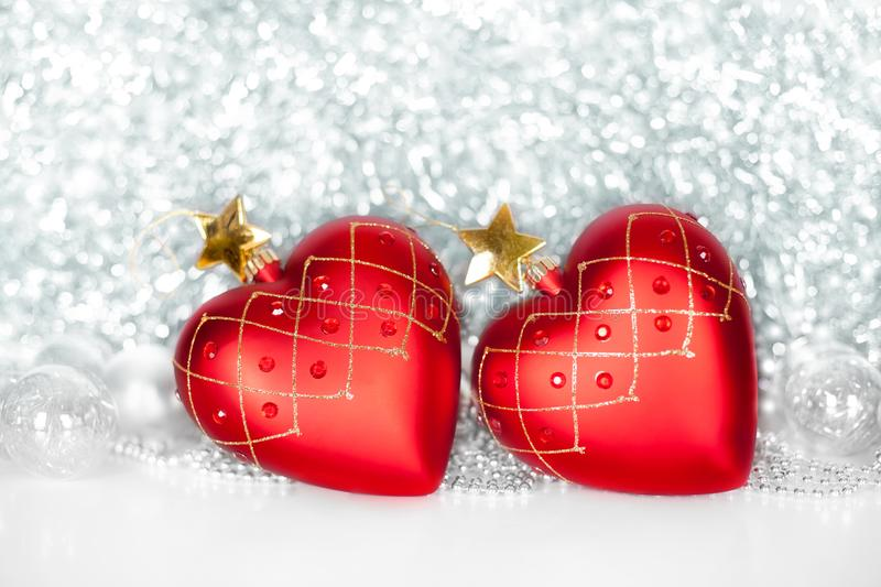 Two red Christmas tree glass balls in the shape of heart with golden stars and silver and red balls on shiny sparkling tinsel stock photo