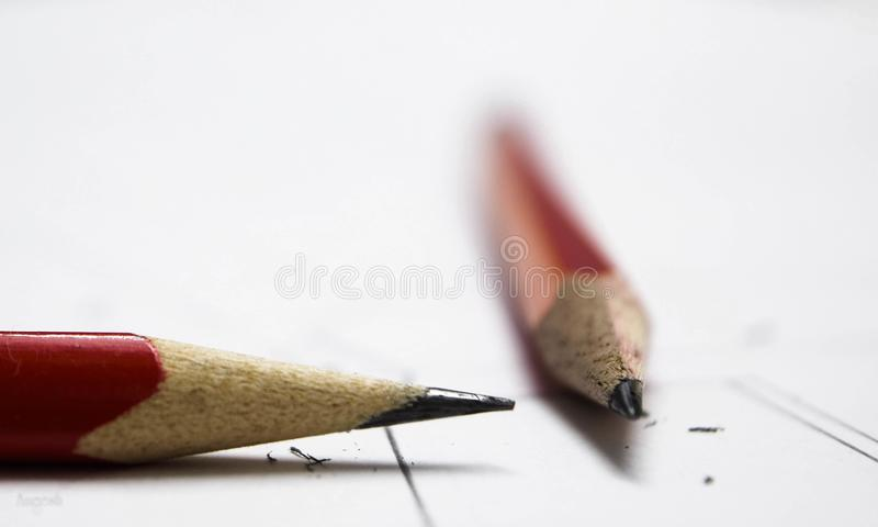 Two pencils meeting at a point. Two red colored wooden pointed pencils meeting at a point royalty free stock photo