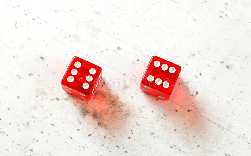 Two red craps dices showing Boxcars or Midnight double number six overhead shot on white board.  royalty free stock photos