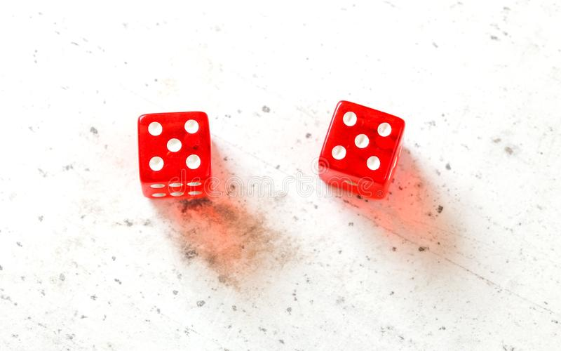 Two red craps dices showing Hard Ten double number five overhead shot on white board.  royalty free stock images