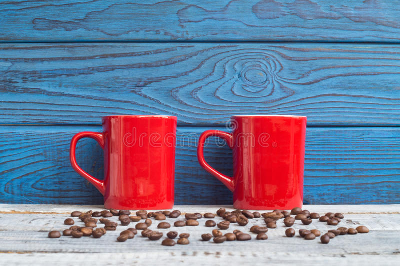 Two red cups and coffee beans on a background of blue boards royalty free stock photo