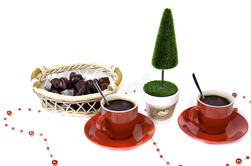 Two red cups of coffee tree and a basket of chocolate. royalty free stock image