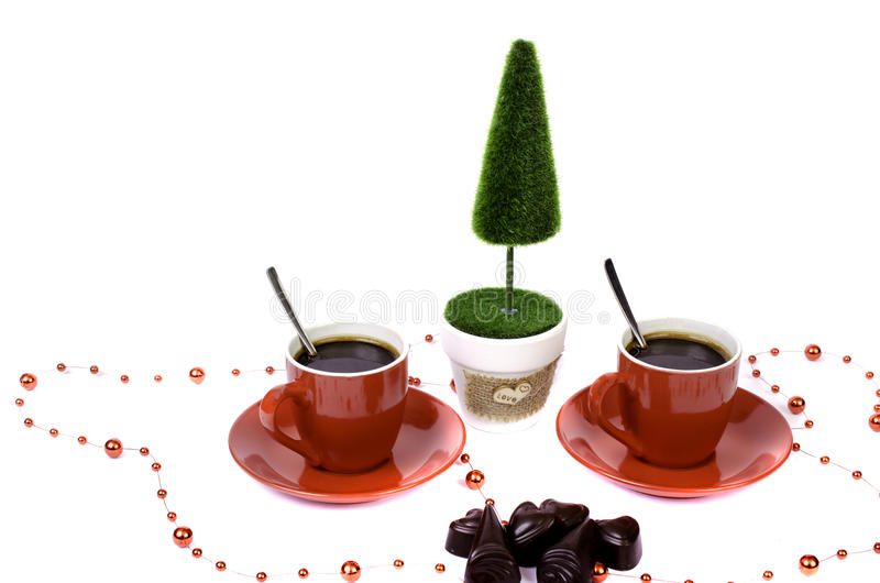 Two red cups of coffee tree and a basket of chocolate. stock photos
