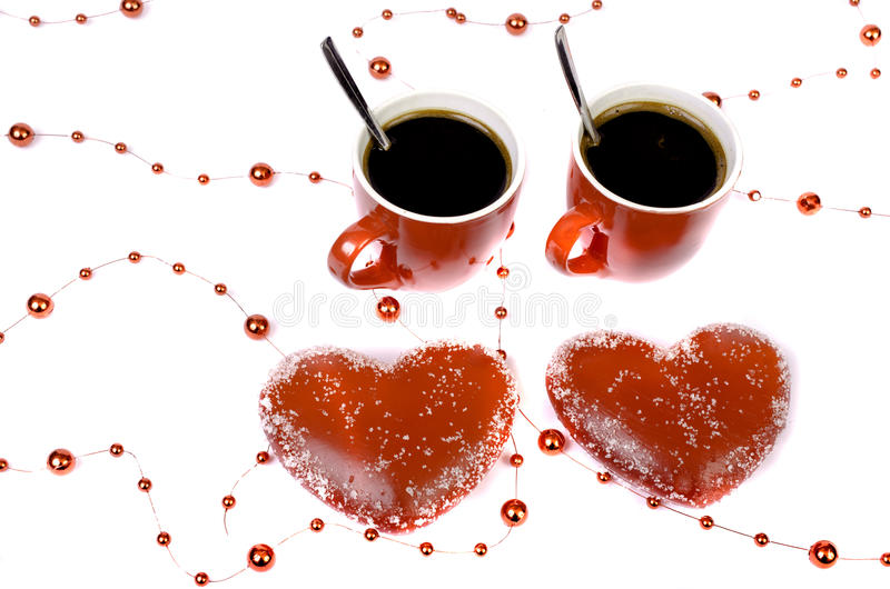 Two red cups of coffee and two hearts on a white background. stock image