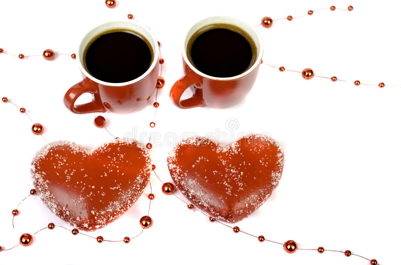Two red cups of coffee and two hearts on a white background. stock images