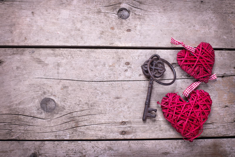 Two red decorative hearts and key on vintage wooden background stock photo